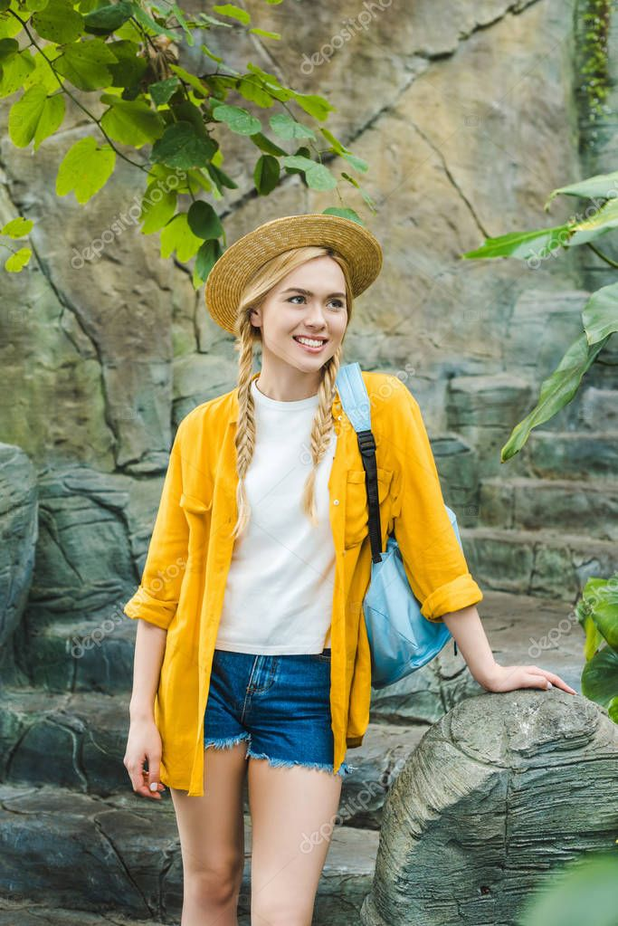 beautiful young woman in straw hat on stone stairs in park