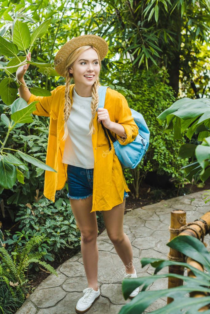 beautiful young woman in stylish clothes walking by park with tropical plants