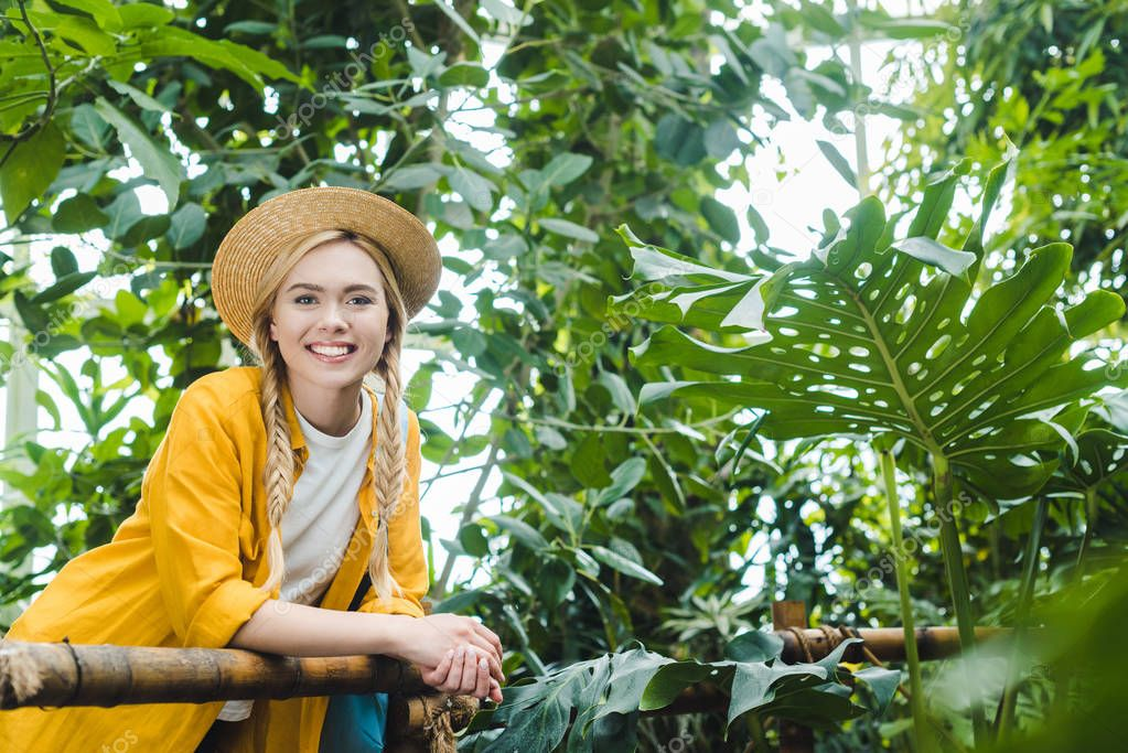 beautiful young woman in straw hat spending time in botanical garden