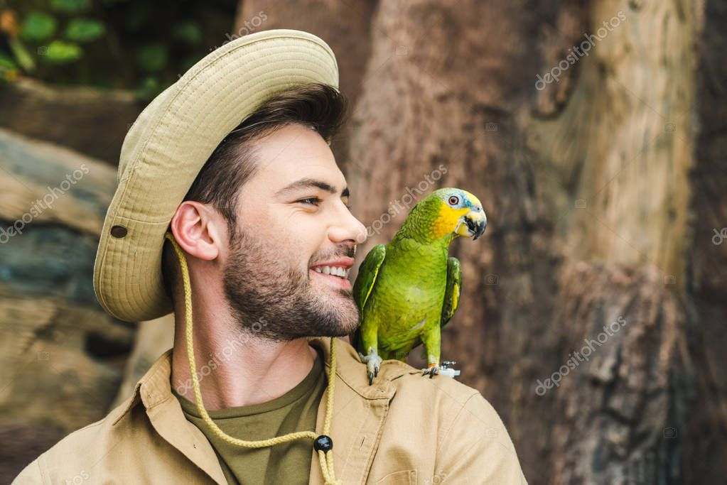 handsome young man with parrot on shoulder in jungle