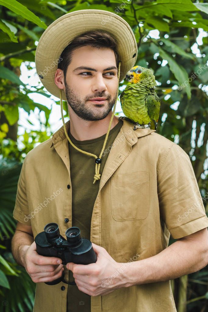 handsome young man in safari suit looking at parrot on shoulder in jungle