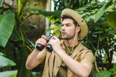 Photo shocked young man with parrot on shoulder and binoculars in jungle