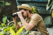 Fotografie handsome young man with parrot on shoulder looking through binoculars in jungle