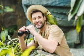 Fotografie handsome young man with parrot on shoulder and binoculars looking at camera