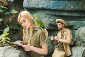 Fotografie attractive young woman in safari suit with parrot and map navigating in jungle while her boyfriend looking through binoculars