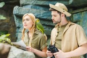 Fotografie beautiful young couple in safari suits with parrot trying to navigate in jungle
