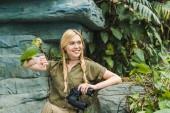 Fotografie glückliche junge Frau in Safari Anzug mit Papagei hocken auf Arm im Dschungel
