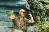 Fotografie glückliche junge Frau in Safari Anzug mit Papagei hocken auf Arm Blick durch ein Fernglas im Dschungel