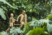 Fotografie active young couple in safari suits holding hands and hiking in jungle