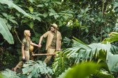 Photo active young couple in safari suits holding hands and hiking in jungle