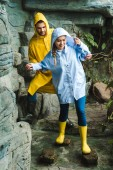 happy young couple in raincoats walking by jungle