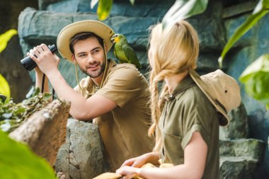 young man in safari suit with parrot on shoulder flirting with woman while hiking in jungle