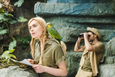 beautiful young woman in safari suit with parrot and map navigating in jungle while her boyfriend looking through binoculars