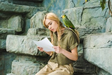 beautiful young woman in safari suit with parrot on shoulder and map sitting on rocks