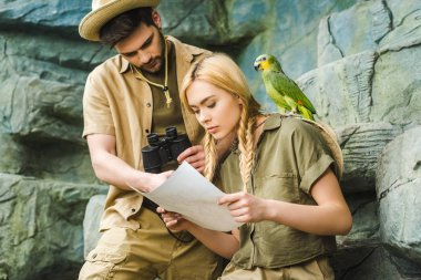 Beautiful young couple in safari suits with parrot hiking in jungle stock vector