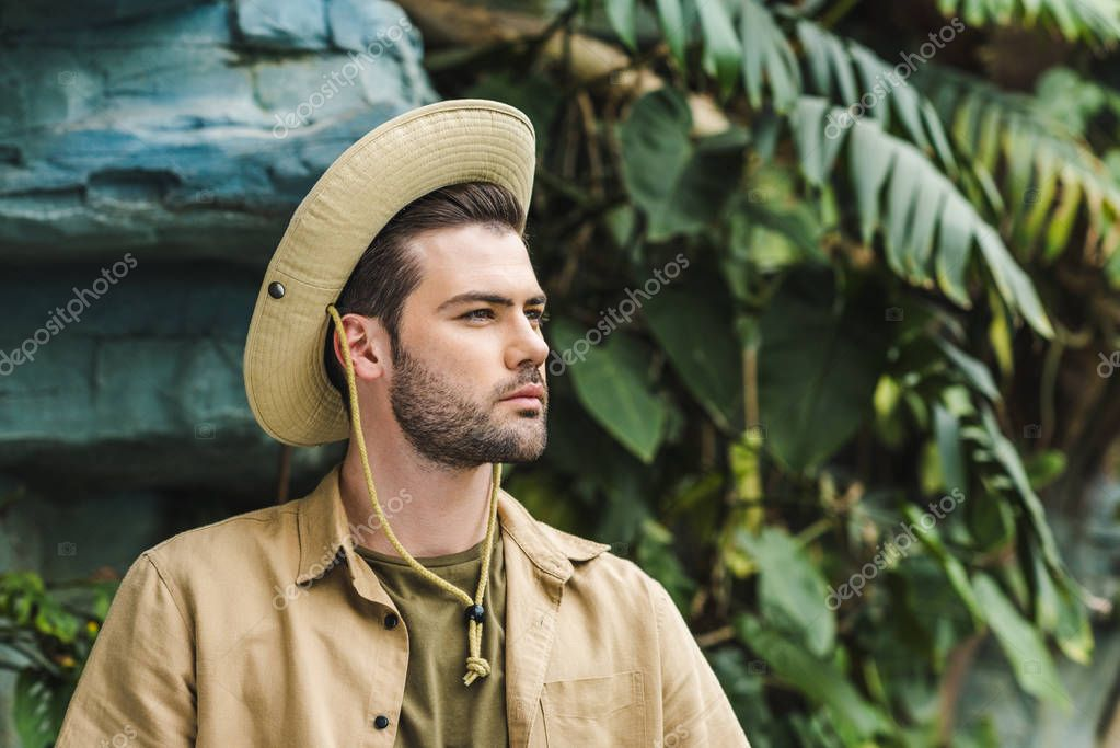 handsome young man in safari suit and hat looking away in jungle