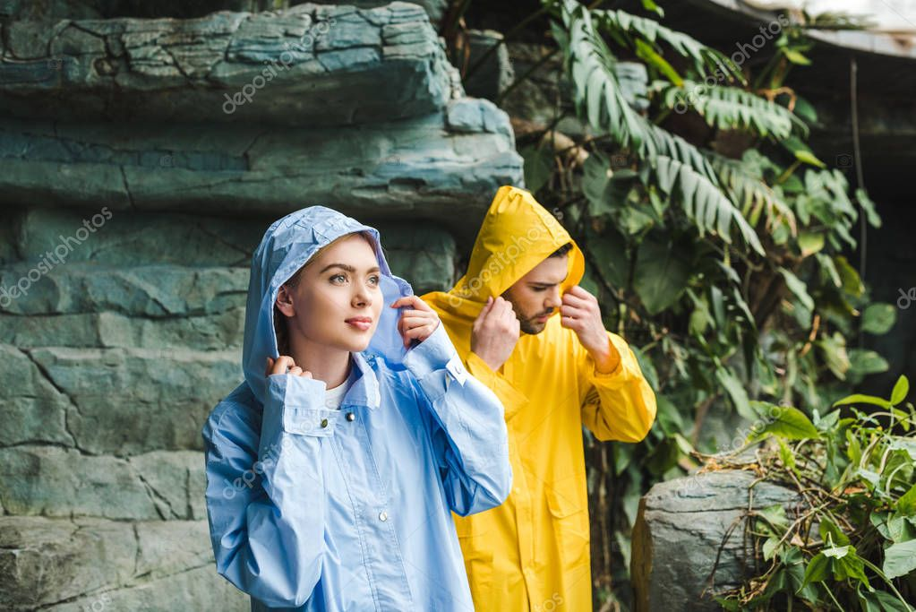 beautiful young hooded couple in raincoats in jungle