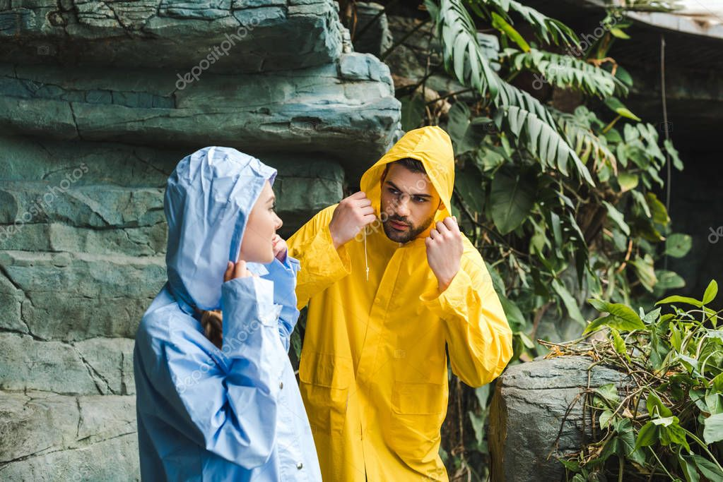 attractive young couple in raincoats in jungle