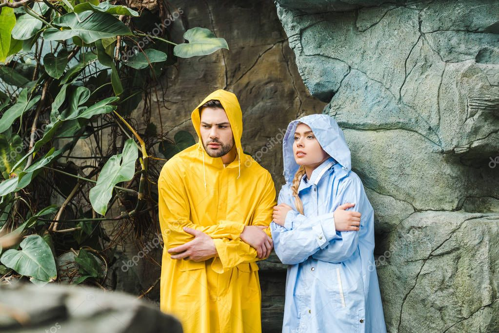 frozen young couple in raincoats under rocks in jungle