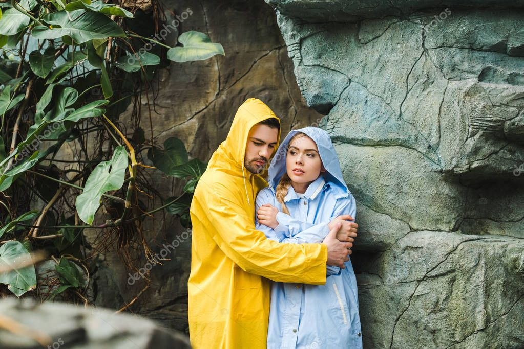 frozen young couple in raincoats embracing and trying to warm up under rocks in jungle