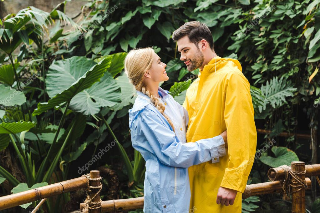 beautiful young couple in raincoats embracing at rainforest