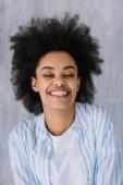 Happy usměvavou americkou afričanku na šedou stěnu pozadí