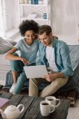 Fotografie Smiling multiracial couple looking at laptop screen while sitting on bed