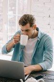 Pohledný muž pití kávy při práci na notebooku doma