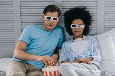 Multiracial couple in 3d glasses watching movie at home with popcorn