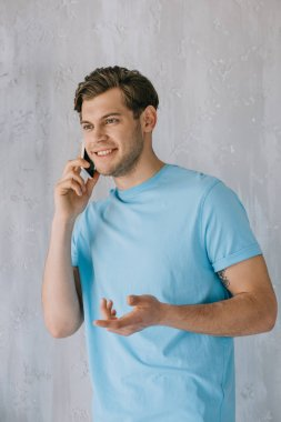 Young man talking on the phone by gray wall stock vector