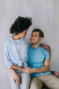 Young multiracial couple hugging while sitting in chair