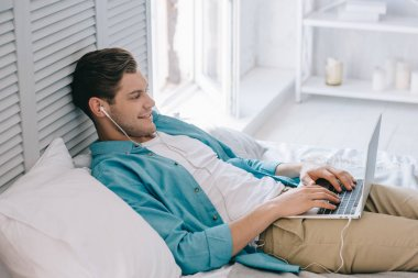Smiling man in earbuds using laptop while lying on bed at home