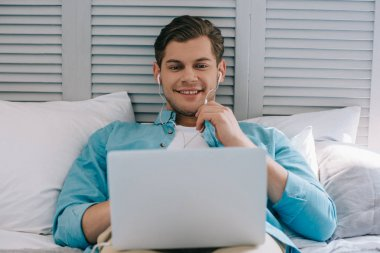Young man in earbuds using laptop while lying on bed