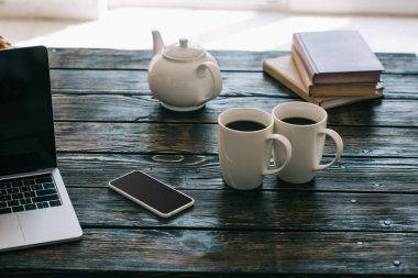 Cups and teapot on wooden table with laptop and smartphone