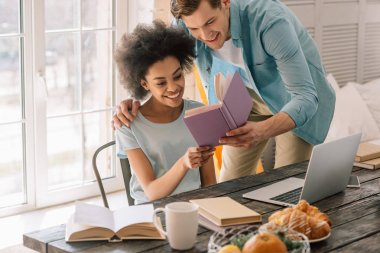 Multiracial young couple reading book by table with laptop