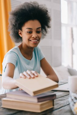 African american young woman choosing book from stack on table
