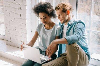 Cam kenarında otururken dizüstü bilgisayar ekranına bakarak çok ırklı Çift