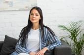 Fotografie Porträt der jungen attraktiven Frau, Blick in die Kamera beim Stillstehen auf Sofa zu Hause