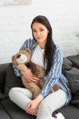 Photo portrait of smiling woman with teddy bear resting on sofa at home