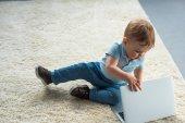 Malý chlapeček s notebookem sedět na podlaze doma