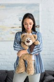 Fotografie portrait of smiling attractive woman with teddy bear in hands at home