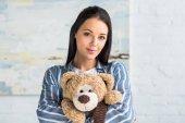 Fotografie portrét mladé atraktivní ženy s plyšovým medvědem v rukou při pohledu na fotoaparát doma