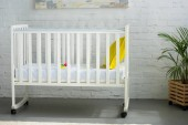 Photo close up view of empty baby crib with yellow pillow in room