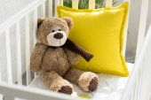 Photo close up view of teddy bear and yellow pillow in baby crib at home