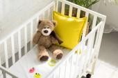 Fotografie pohled z vysokého úhlu Medvídek, jiné hračky a žluté polštář v dětské postýlce doma