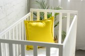 Fotografie zblízka pohled na prázdnou postýlkou s žlutým polštářem v pokoji