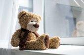 Fotografie zblízka pohled roztomilý medvídek na okenním parapetu