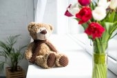 Photo selective focus of teddy bear and bouquet of tulips in vase o window sill at home