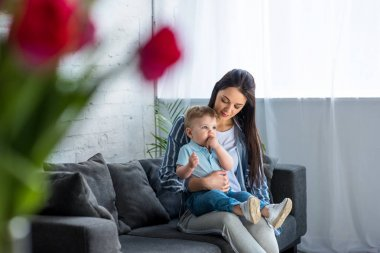 selective focus of mother with adorable baby boy on hands sitting on sofa at home