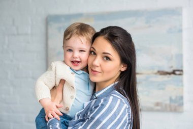 portrait of young mother holding cheerful adorable baby boy in hands at home